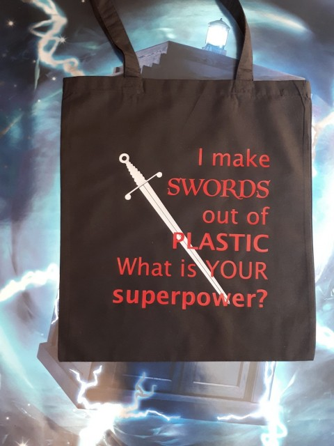 "Handlenett / veske med teksten: ""I make swords out of plastic, what is your superpower?"""